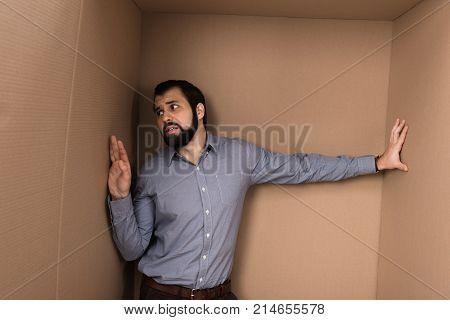 stressed lonely man in big cardboard box