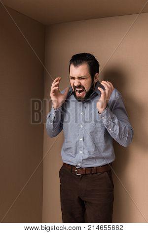 stressed man yelling in big cardboard box