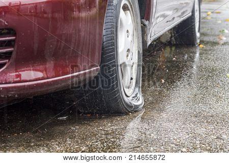 Car flat tire on street in rainy day