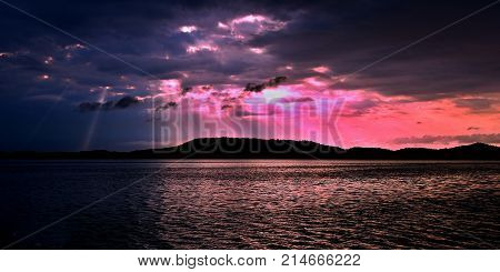 Delightful inspirational brightly coloured cloudy sea water panoramic sunrise seascape featuring distinctave crepuscular rays with ocean water reflections.