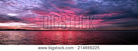Delightful inspirational brightly coloured cloudy sea water tropical panoramic sunrise seascape with ocean water reflections. New South Wales Australia.