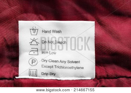 Washing instructions clothes label on red cloth closeup