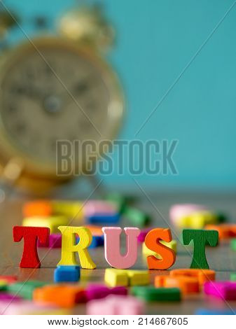 Trust. English alphabet made of wooden letter color. Alphabet trust on wooden table and vintage alarm clock and background is powder blue.