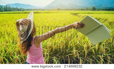 Asian women relax in the holiday. Read book on vacation. Write a study of natural garden rice field garden.