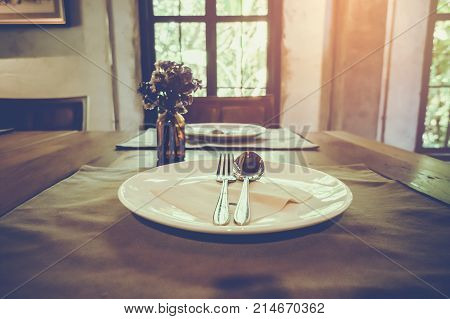 Luxury dining table. Closeup of table in modern dining room with table set and vase of flower. Image contain certain grain or noise. Vintage film filter effect.