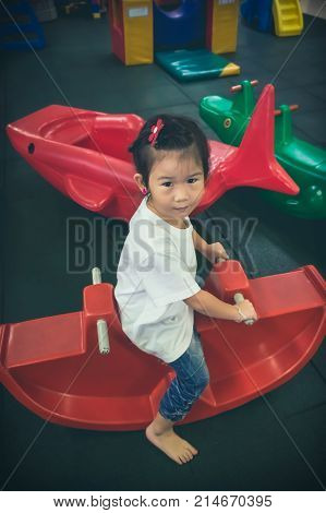 Asian Girl Sitting On Red Plastic Seesaw. Vintage Film Filter Effect.