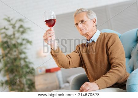 Wine expert. Low angle shot of a serious elderly man sitting in a chair and concentrating on a glass of red wine while examining it at home.