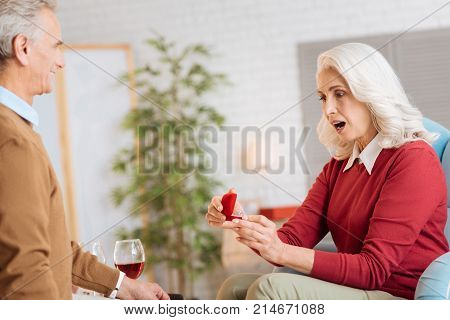 What is that. Amazed retired woman keeping her mouth wide opened after receiving a gift from her soulmate and looking at the ring.