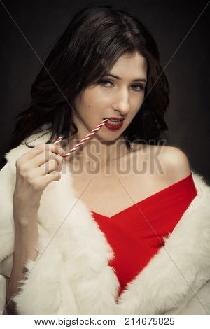 Young woman wearing a faux fur wrap at Christmas holding a candy cane