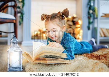 A Smiling Child Reads A Book At Home. Concept New Year, Merry Christmas, Holiday, Vacation, Winter,
