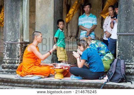 Siem Reap, Cambodia - Dec 10 2016: Buddhist Monk Give A Wish To People In Angkor Wat. A Famous Histo