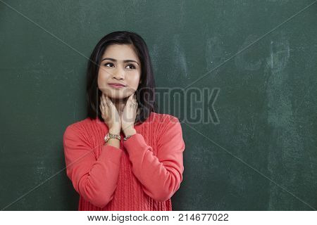 Thinking woman by blackboard. university college student pensive and contemplating looking up to the at empty blank copy space on chalkboard black background. Asian malay 20s.