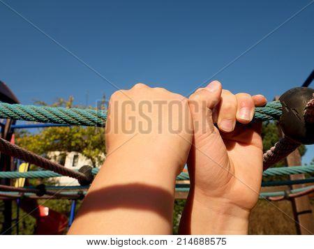 Boy Holding On Blue Rope Bar In Kinder Garden Playground