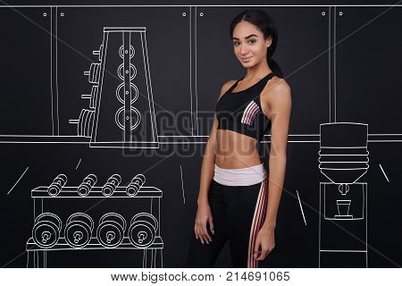 Train your muscles. Positive content woman training in a gym and expressing gladness while maintaining healthy way of life