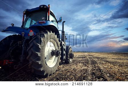 Tractor working on the farm, a modern agricultural transport, tractor at sunset, fertile land, modern tractor closeup, cultivation of land