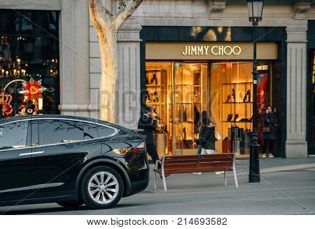 BARCELONA SPAIN - NOV 13 2017: Luxury electric Tesla Model X SUV parked in front of the Jimmy Choo fashion boutique clothes store on Avenue Diagonal