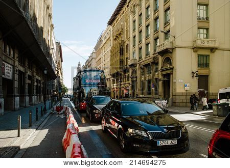 BARCELONA SPAIN - NOV 12 2017: Ruta Roja Sightseeing Barcelona Hop On Hop Off bus with tourists and Skoda Superb car in traffic jam in Barcelona