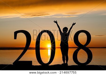 2018 New Year silhouette of a girl with hands raised at the beach during golden sunrise or sunset with copy space. Concept of joy praise worship connection with nature.