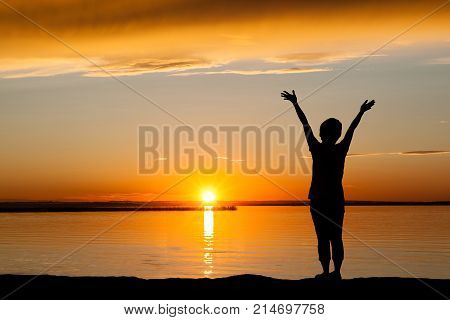 Silhouette of a girl with hands raised at the beach during golden sunrise or sunset with copy space. Concept of joy praise worship connection with nature.