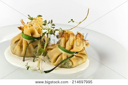 Crepe dumplings with spinach and mozzarella on white background