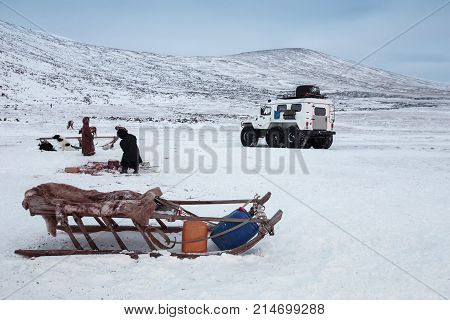 Siberian sledge, against the background of an all-terrain vehicle and people. Russia, Siberia, Yamal poster