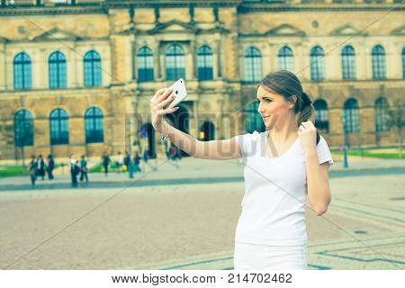 Girl makes photos shots of european city Dresden and selfie of background old German town