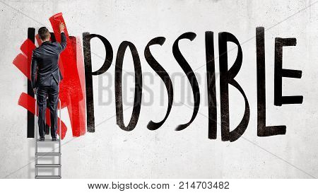 A businessman stands on a stepladder and hides the word Impossible written on the wall using a red paint roller. Business and success. Goals and planning. Impossible made possible.