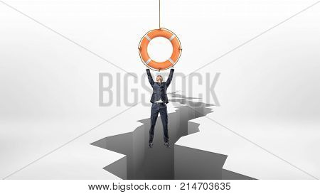 A tiny businessman holds on to a red life buoy hanging above a large earthquake rift. Last chance. Keep business running. Last resort.