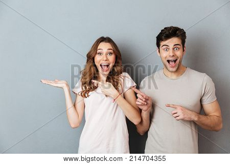 Portrait of an excited satisfied couple standing and pointing fingers away at copy space isolated over gray wall background