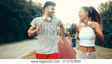 Athletic couple jogging in nature in good spirit