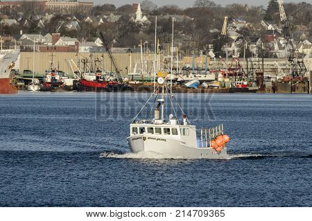 New Bedford Massachusetts USA - November 21 2017: Fishing boat Slave Driver crossing New Bedford harbor