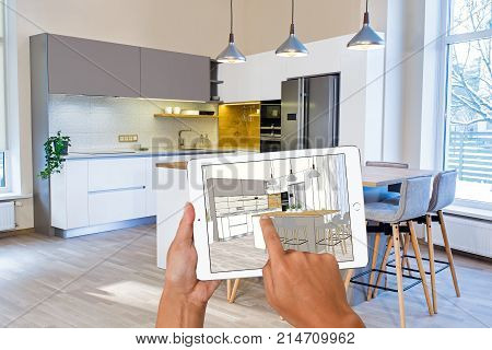 Hands holding tablet with kitchen interior sketch. In the background real finished kitchen interior design. Kitchen presentation.