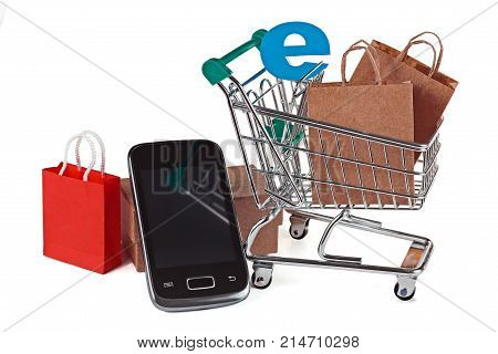 Shopping trolley with shopping bags and smartphone. A conceptual image of a purchase on the Internet and payment through a smartphone. Isolated on white.