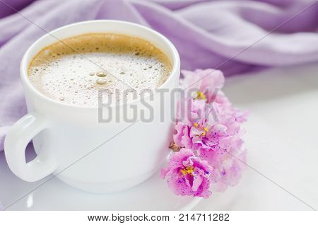 White cup of morning coffee or cappuccino and delicate pink, purple, lilac flowers. Mother's day concept. Cozy breakfast.