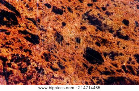 Obsidian mineral stone texture pattern macro view. Beautiful volcanic glass dark-red brown color with black spots background