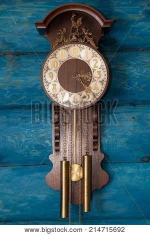 Old antique clock on a blue wooden background.