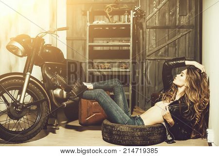 Sexy Woman Lying In Dirty Rubber Tire On Floor