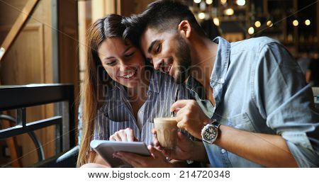 Young attractive cheerful couple on date in coffee shop looking at tablet