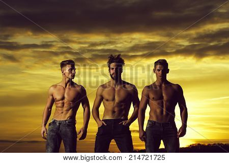 three men or bodybuilders in jeans handsome young male athlete people with sexy muscular torso six packs abs biceps triceps outdoors in sunset sky