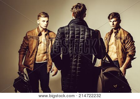 Muscular Macho Men Holds Travel Bag, Suitcase, Backpack