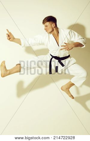 Handsome Karate Master Jumping In Fighting Stance