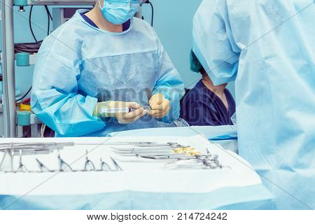 Close Up Hands Of Surgery Assistant Prepearing Steralized Surgical Tools For Surgery Operation. Sele