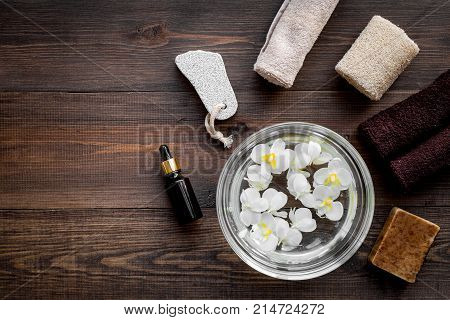 Bath in bowl with tropical flowers for foot spa, pumice stone, soap and oil on dark wooden background top view.