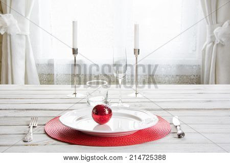 Christmas place setting with white dishware cutlery silverware and red decorations on white wooden board in ligth interior near the window. Christmas candlestick with red candles as decor.