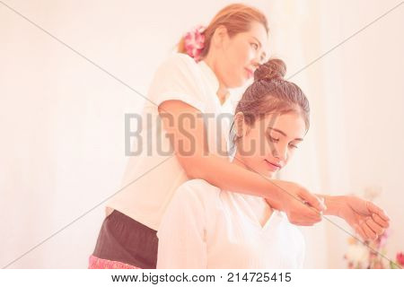 Thai Masseuse is massaging a woman should in Thai Massage Spa position