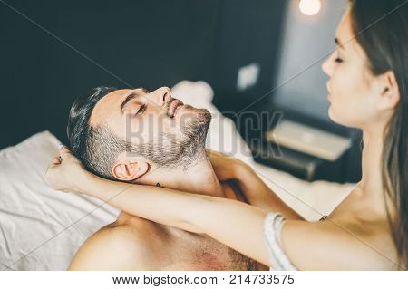 Young passionate couple having sex on the bed at home - A sensuality girl pulling her boyfriend's hair - Concept of role playing game of intimate lovers in the bedroom - Focus on man's face