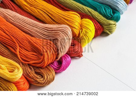 Group of colorful yarn or floss for needlework or knitting on white background