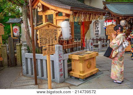 Kyoto, Japan - April 24, 2017: woman wearing kimono prays at popular Jishu Jinja Temple behind Kiyomizu-dera, a shrine dedicated at god of love and revered as the Cupid of Japan.