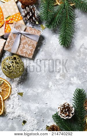 christmas frame with spruce branches cones gift boxes with a ball on a gray concrete background copy space flat lay