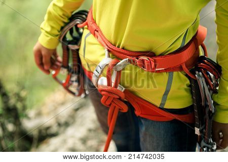 rock climber standing with climbing gears and rope